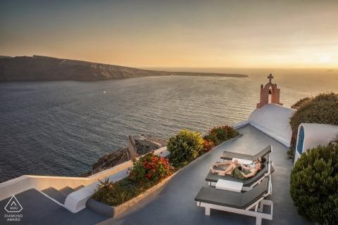 Ce couple de fiancés se détend au bord de l'eau au coucher du soleil lors de la séance de fiançailles à Santorin