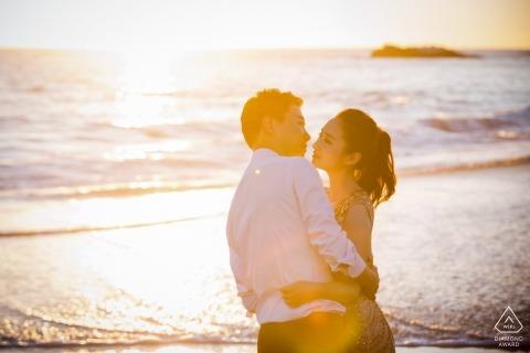 Un homme et une femme se tiennent sur une plage ensoleillée aux États-Unis lors de cette séance photo précédant le mariage par un photographe de la ville de Hangzhou.