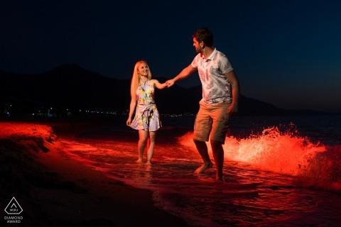 Verlobte Paare, die am Abend in das Meer für ihre Verlobungssitzung gehen