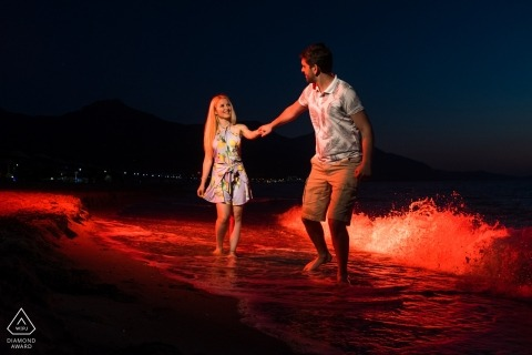 Engaged couple walking in the sea at evening for their engagement session
