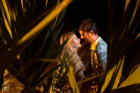 Enagaged couple looking at each other behind a palm tree for their engagement shoot