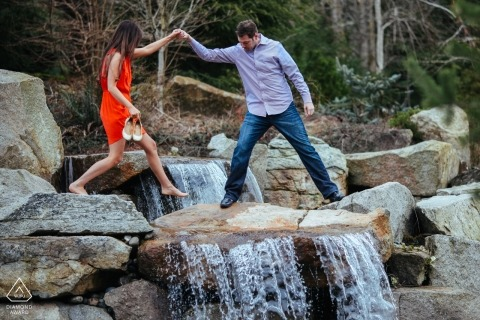 Bonney Lake, WA Engagement Photography Session - Man helps his wife to be across a waterfall