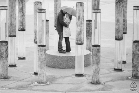 A couple kisses under an umbrella surrounded by water fountains in Tacoma, Washington