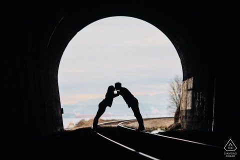 Tacoma, Washington Engagement Photography Session | Het paar leunt binnen voor een kus in een oude treintunnel