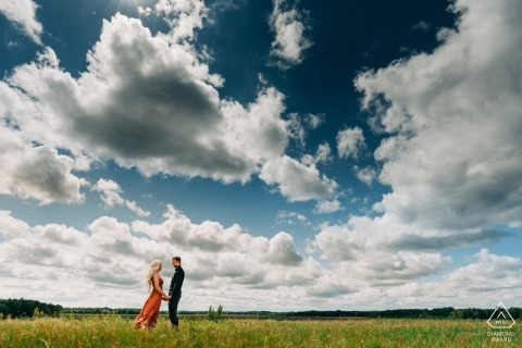 Overjissel engagement photographer caught this image of a couple holding hands in a sunny meadow