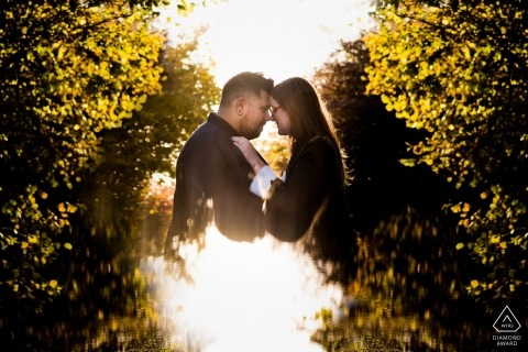 Northhamptonshire engagement photographer designed this sunkissed portrait of a couple embracing in the hedges near Twywell Gullet