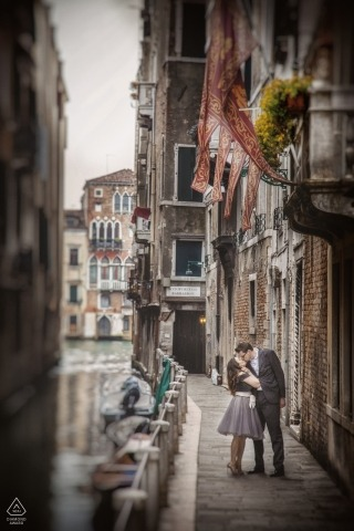 This prewedding portrait of a couple kissing on a city street was created by a Venice wedding photographer