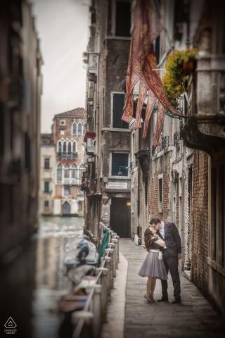 Dieses Porträt eines Paares vor der Hochzeit, das sich auf einer Stadtstraße küsst, wurde von einem venezianischen Hochzeitsfotografen geschaffen