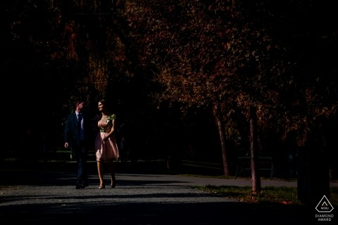 Romania engagement photographer caught the action in this photo of a couple walking happily through IOR park in Bucharest at night