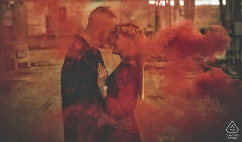 Liguria engagement photographer designed this portrait of a couple embracing while shrouded in red smoke in Bolano