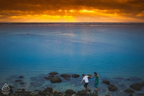 Bali couple walking in the sunset on the beach rocks for engagement portrait
