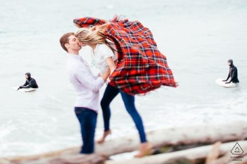 Seattle, Washington Pre Wedding Photo Session - Man die zijn verloofde vasthoudt terwijl surfers op de achtergrond zijn