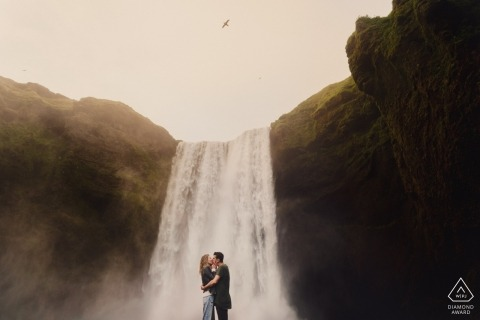 Engaged couple kissing with large Iceland waterfall in the background and a bird in the air