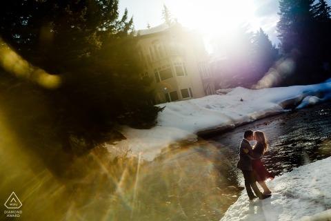 Vail, CO Engagement Shoot - In piedi vicino al fiume Eagle a Vail mentre gli ultimi frammenti di sole spruzzano attraverso gli alberi sempreverdi per questa sessione di fidanzamento invernale.
