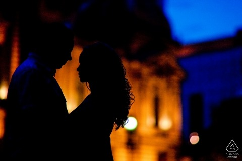 Engaged couple posing in front of the night illuminated Cec Palace in Bucharest for pre wedding portraits.