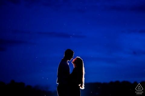 Rixey VA Farm Engagement Portrait-Sitzung - Das Paar umarmt sich nach Sonnenuntergang und der Himmel ist beleuchtet