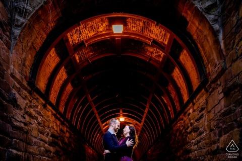 Wilkes Tunnel, Altstadt Alexandria VA Verlobungsshooting - Ein Paar umarmt sich am Eingang des Tunnels