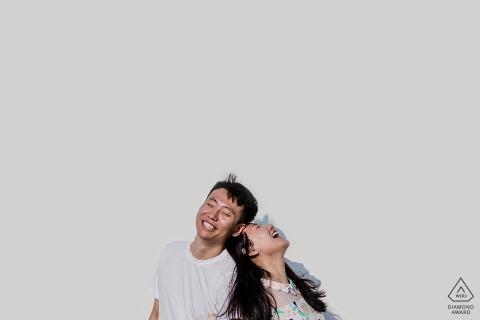 Couple de Chine Liaoning riant contre le mur blanc lors d'une séance photo de fiançailles