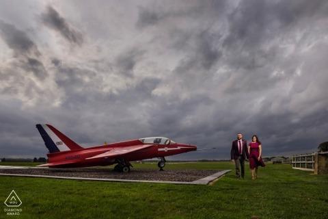 Portrait de fiançailles de couple avec robe rouge et avion rouge à l'aéroport de Cotswald, Royaume-Uni