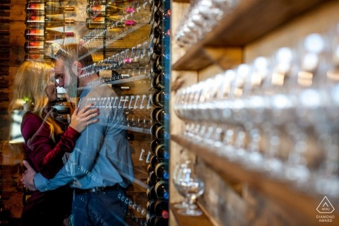 Wild Terra Cider Bar Fargo, North Dakota - Engaged couple embrace at the bar during engagement photo session indoors