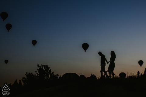 Kapadocja, Turcja Portrety zaręczynowe - sylwetka pary spacerującej na wzgórzu i balonów na ogrzane powietrze na pierwszym planie