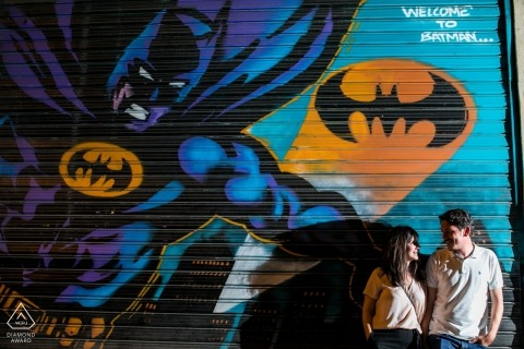 Athens, Greece Engagement Photos - Couple looking each other in front a big Batman mural