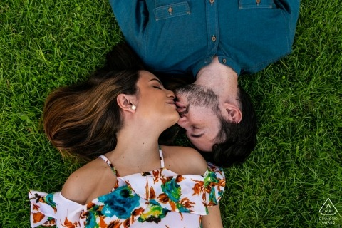Venezuela Engagement Photos - Un couple de Caracas allongé dans l'herbe et s'embrassant