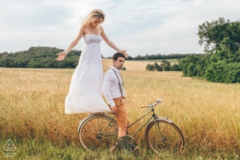 Gers, South of France Engagement Photographer - A couple on a bicycle pose during pre-wedding portrait session.