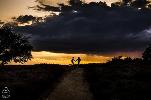 Blaricum verlovingsfotoshoot van paar met donkere wolken in aantocht.