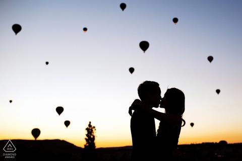 Cappodocia, photographe de fiançailles en Turquie capturant un baiser à un lever de soleil magique avec des ballons
