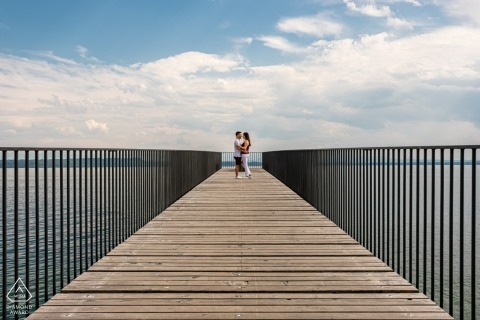 Switzerland engagement portrait of a couple at the end of a boardwalk extending out into the water.