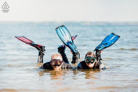 Popowo海灘放置在與風鏡和飛翅的水中的夫婦的訂婚照片。