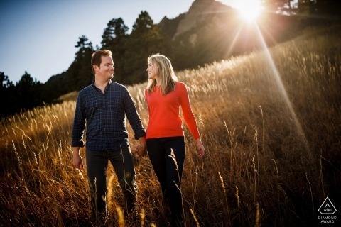Boulder Colorado Engagement Photography of a couple walking near the Flatirons while getting kissed by the last bit of sun.