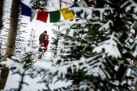 Engagements during a blizzard while this couple stands framed below some prayer flags.
