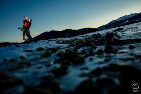 Lifting his fiance in the frigid temps of winter while taking a walk next to Dillon Reservoir during an engagement session.
