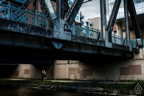 A couple stands under a pedestrian bridge in downtown Denver for their urban engagement session
