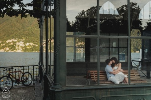 Couple sitting in indoor bench in como lake for pre wedding portraits.