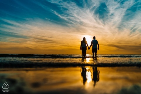 Engeland Beach Sunset Engagement Session met de reflectie van het paar in het water
