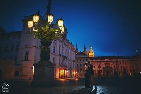 Hradcanske Namesti, Castillo de Praga, República Checa Retratos previos a la boda | Una pareja comparte un beso a finales de la noche de verano debajo de las impresionantes lámparas de gas en el Castillo de Praga