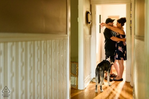 Engaged couple hugging in their home as their dog watches in this Montreal engagement photoshoot