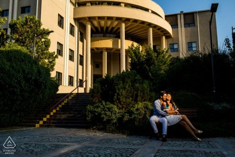 Engaged couple is sitting in front of a big building during their Ankara photo session.