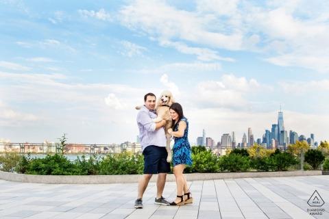 Standardpudel springt während ihrer Hoboken NJ Verlobungsfotosession am Steven's Institute of Technology in die Arme eines Paares