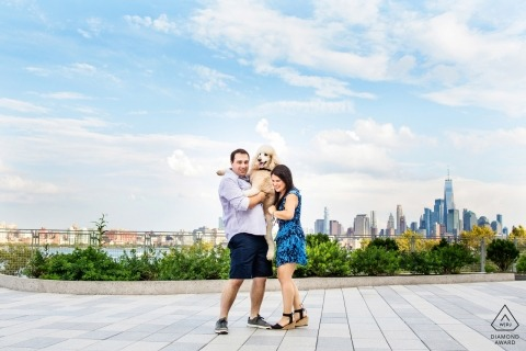 Standard poodle jumps up into arms of couple at Steven's Institute of Technology during their Hoboken NJ engagement photo session