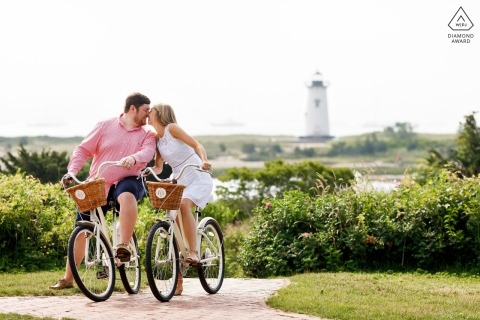 Edgartown, MA engaged couple riding bikes during portrait session at lighthouse