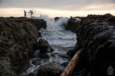 Laguna Beach CA Engagement Photographer - Couple walking on rocks at beach