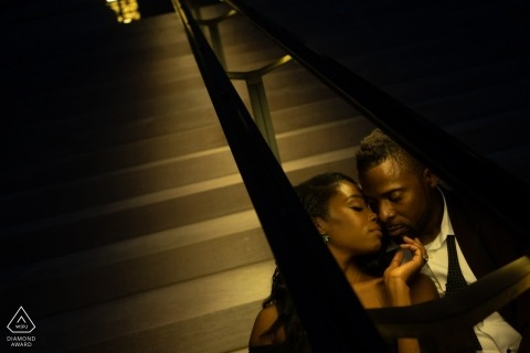 Couple sitting on steps under hand railing light for engagement portraits at Washington DC National Gallery of Art