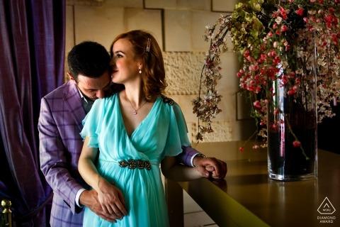 Pareja abraza a la entrada del restaurante Il Calcio durante una sesión de retratos de compromiso en Bucarest