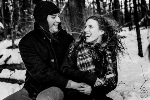 The Fells Reserve Massachusetts Pre Wedding Portraits - Het verloofde paar lacht samen tijdens hun winterverlovingssessie in het Fells Reserve