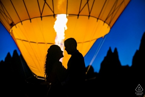 Cappadocia Turkey couple in front of the balloon fire during prewedding engagement portrait session at dusk