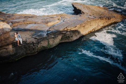 San Diego, California Engagement Photo Session | Couple sitting down and holding hands on the cliffs of ocean